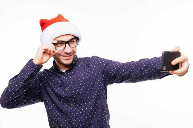 흰 벽에 고립 된 크리스마스 산타 모자 서 입고 젊은 행복 감정적 인 남자