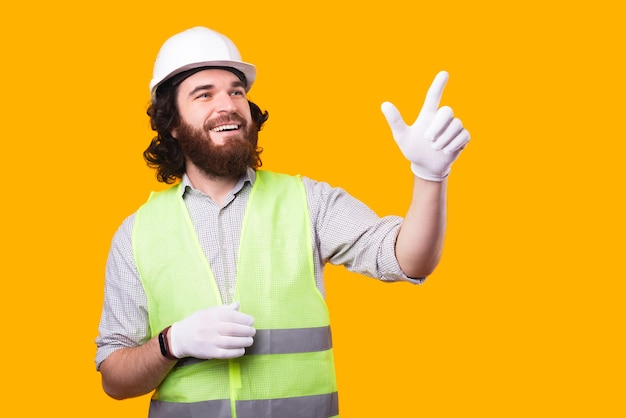 A young happy engineer is looking away trying to touch something on a free space near a yellow wall