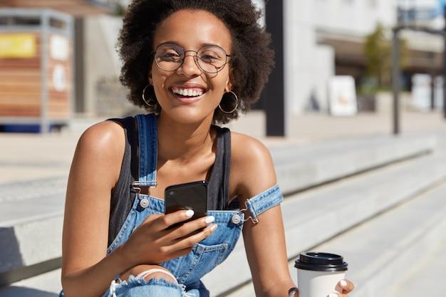 La giovane femmina etnica felice controlla la posta elettronica con notifica, sorride ampiamente, posa in ambiente urbano, beve caffè da asporto, chat sul cellulare, gode di una bevanda calda. gioventù, tempo libero, tecnologie