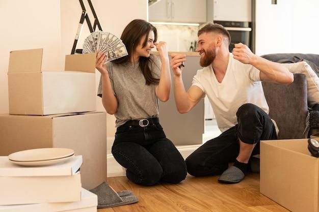 Молодая счастливая европейская пара празднует в новом доме. девушка держит долларовые банкноты. человек, держащий ключ. картонные коробки с вещами. концепция переезда в новую квартиру. молодая семья. интерьер квартиры-студии
