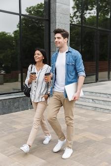 Молодые счастливые возбужденные удивительные любящие студенты пары на открытом воздухе на улице, гуляя, пьют кофе, разговаривают друг с другом.