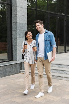 Young happy excited amazing loving couple students outdoors outside at street walking drinking coffee talking with each other.