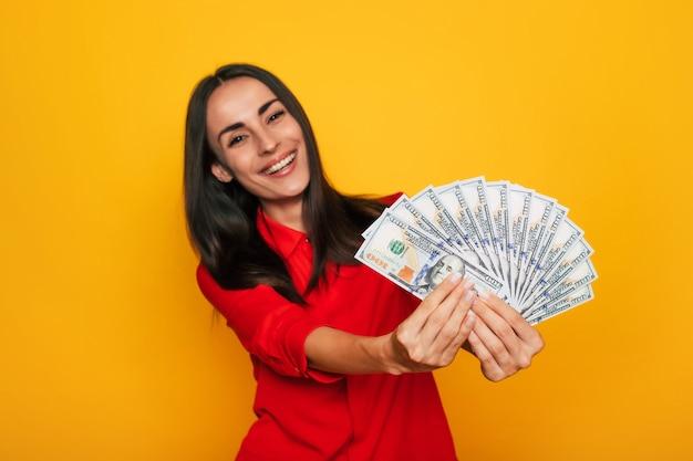 彼女の手にたくさんのお金を持って感情的にカメラを見て、黄色の背景で隔離の楽しみを楽しんでいる若い幸せな興奮した美しい女性