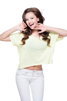 Молодая счастливая выразительная женщина с длинными каштановыми вьющимися волосами позирует