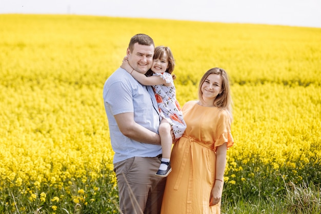 黄色の開花フィールドの中で若い幸せな家族