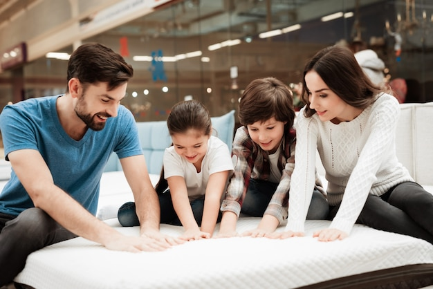 Young happy family choosing mattress together
