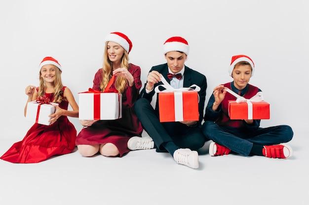 サンタの帽子の子供たちと若い幸せな家族のクリスマス