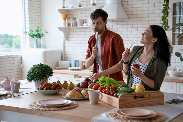 Young happy family couple dancing singing and having fun while preparing healthy food in the modern