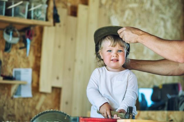 製品のツールを使用して大工のワークショップで若い幸せな家族のお父さんと赤ちゃん