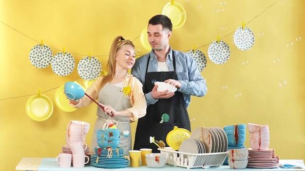 若い幸せな家族は、台所で一緒に働くことを楽しんでいます。コロナウイルスのパンデミックによる自己分離
