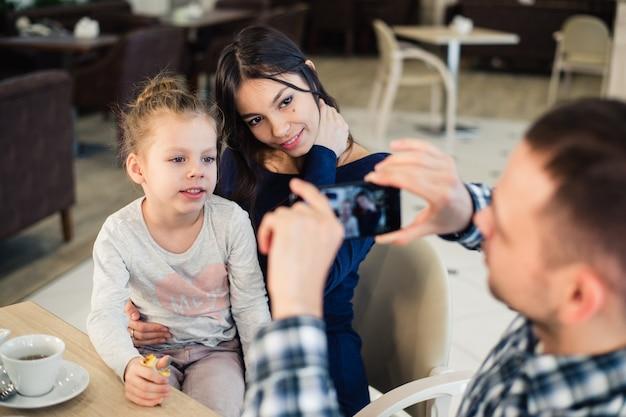 レストランで楽しんでいる若い幸せな家族