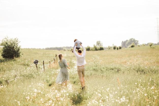 야외에서 여름날 즐겁게 노는 젊은 행복한 가족. 아버지는 어깨에 아들을 안고 있습니다.