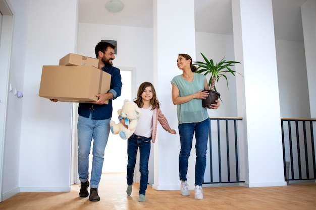 Young happy family holding boxes and flower while moving into new home.