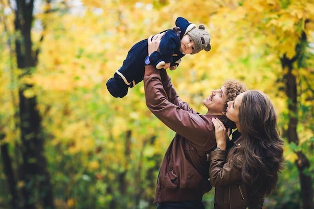 공원에서가 젊은 행복 한 가족. 아버지는 즐겁게 아들을 던졌습니다.