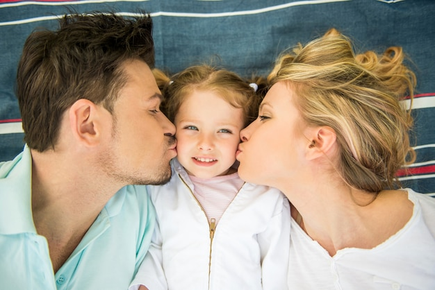 Young happy family kissing little girl.