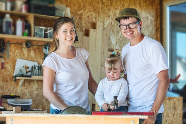 Young happy family mom, dad and baby in the carpentry workshop working with tools