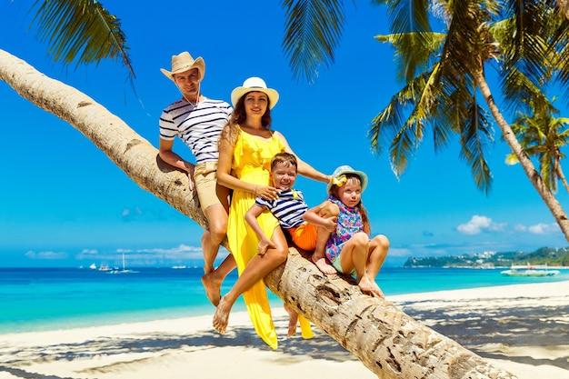 Молодая счастливая семья-мама, папа, дочь и сын веселятся на кокосовой пальме на песчаном тропическом пляже. концепция путешествий и семейного отдыха.