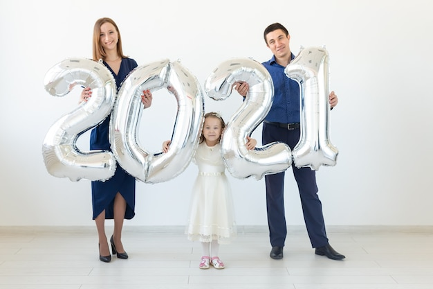 Young happy family mother and father and daughter standing near balloons shaped like numbers 2021