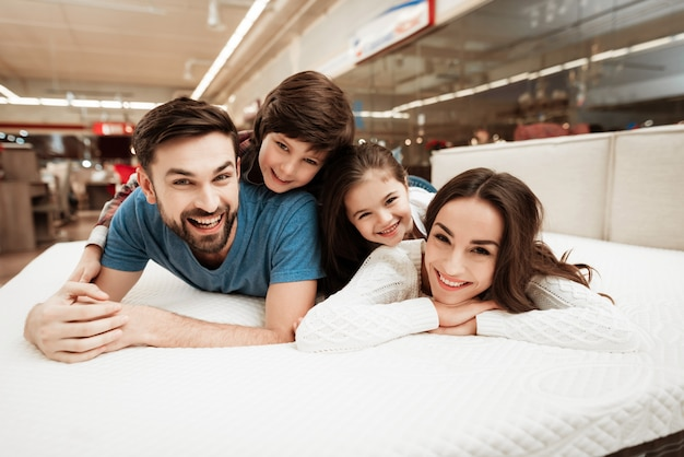Young happy family relaxing on soft bed in store