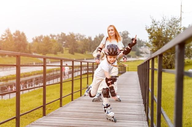 公園で若い幸せな家族のローラースケート。アクティブウォーク。母親と活発な散歩をしている就学前の女の子。ダイナミックフォーカス