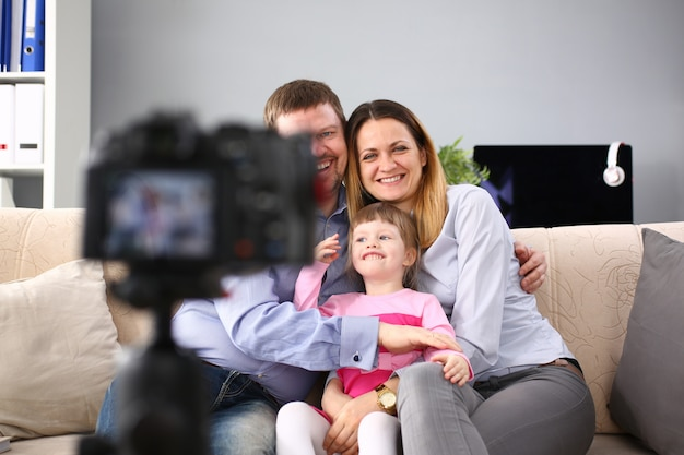 Young happy family sit on couch making photo session portrait