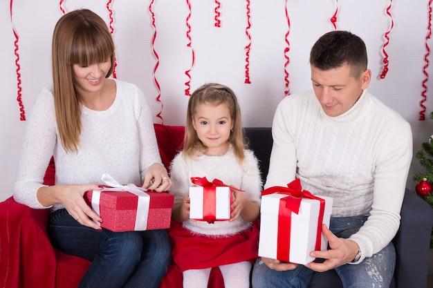 ソファに座って、クリスマスプレゼントを開く若い幸せな家族