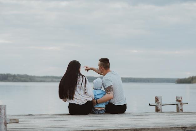 水辺の夏に桟橋に座っている若い幸せな家族