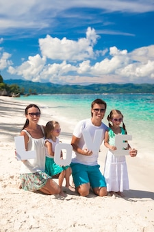 Young happy family and two kids with word love on tropical vacation