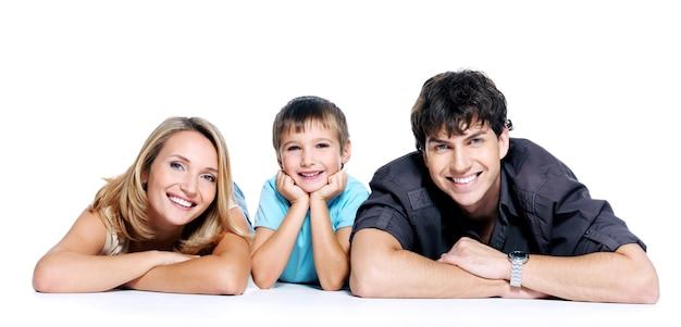 白いスペースでポーズをとって子供と若い幸せな家族