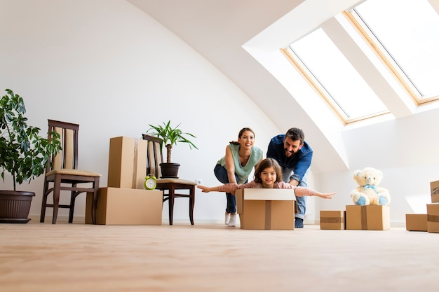 Young happy family with children moving into new house and riding in cardboard box.
