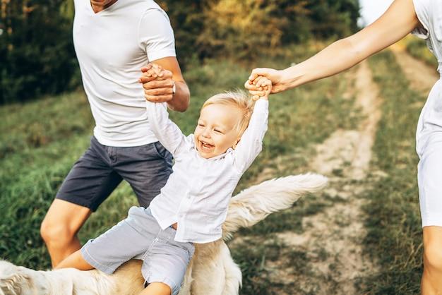 犬と若い幸せな家族は屋外楽しい時を過す