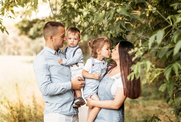 夏の散歩で自然の中で2人の子供を持つ若い幸せな家族。健康的な笑顔のお父さん、お母さんと子供たちが一緒に