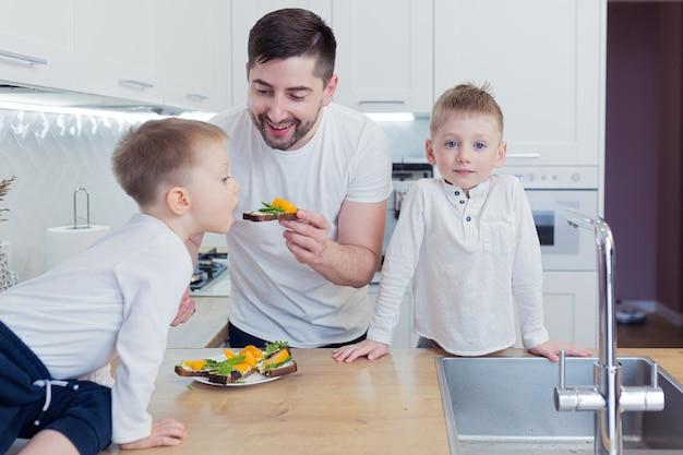 그들의 부엌에서 함께 아침 식사를 준비하는 두 어린 아들과 함께 젊은 행복한 가족