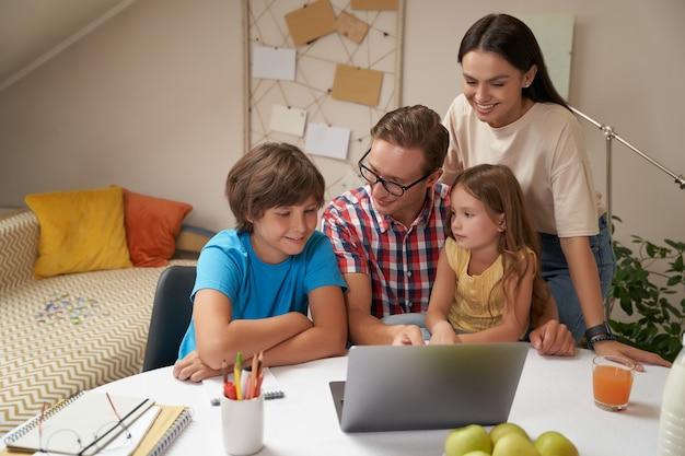 어린 행복한 가족이 함께 노트북 작업을 하거나 숙제를 하거나 공부하는 아이들을 돕습니다.