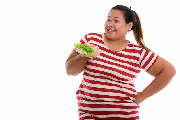 Young happy fat asian woman smiling and posing with lettuce