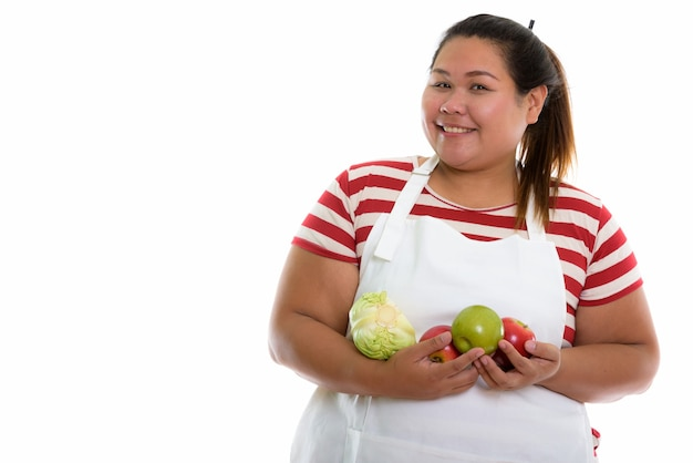 Young happy fat asian woman smiling while holding vegetables