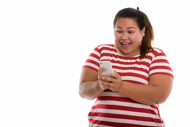 Молодая счастливая толстая азиатская женщина улыбается во время использования мобильного телефона