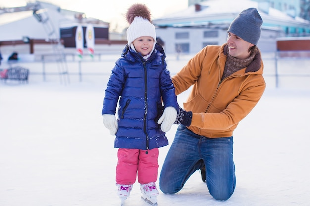 Young happy father and adorable little girl on a skating rink