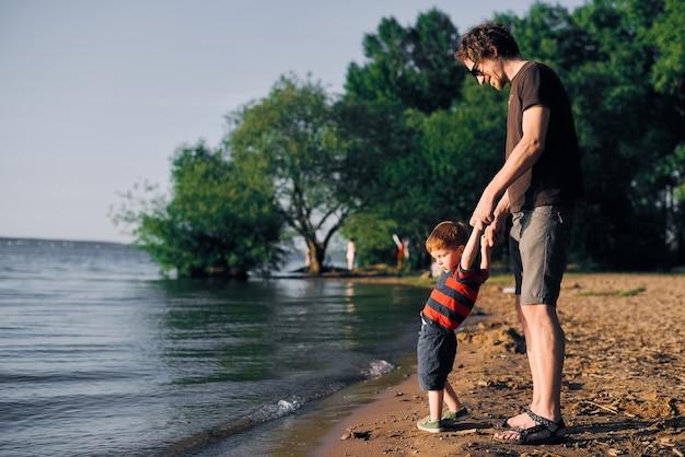 若い幸せな父は彼の幼い息子の手を握って、夏に湖の上を歩きます
