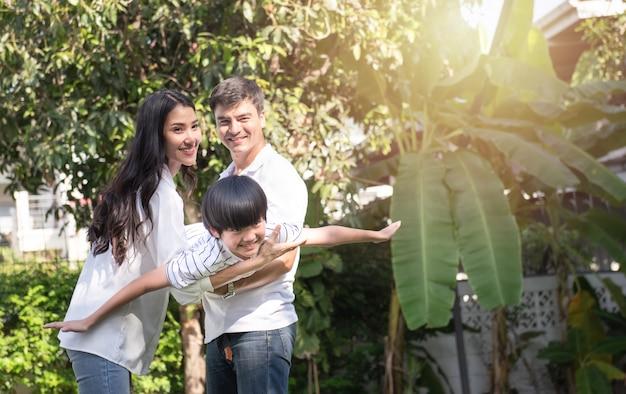 若い幸せな父、母と息子の前の家の庭で一日の時間に公園で遊んでいます。フレンドリーな家族の概念。