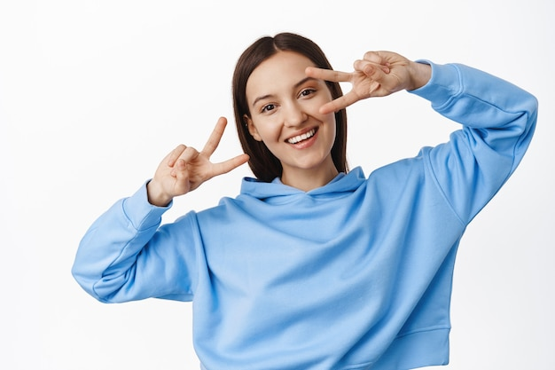 Young happy female in blue hoodie, showing peace v-signs, disco gesture near eyes, dancing and smiling joyful, standing over white wall
