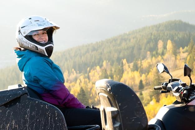 보호용 헬멧을 쓴 젊고 행복한 여성 운전자는 해질녘 가을 산에서 atv 4륜 오토바이를 타고 극한의 라이딩을 즐기고 있습니다.