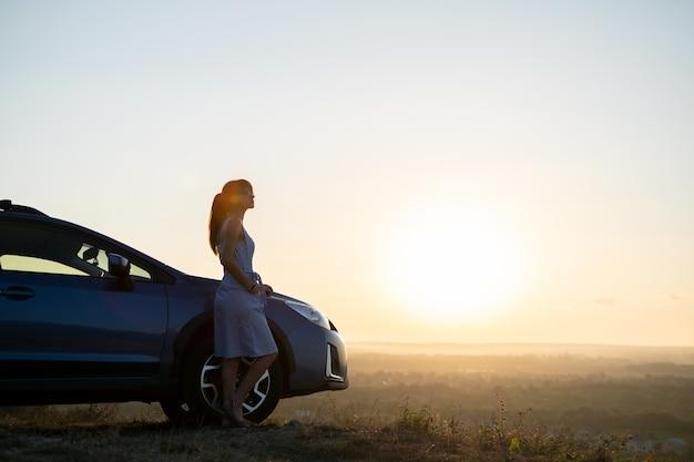여름 자연의 일몰 전망을 즐기는 그녀의 차 근처에서 쉬고 있는 젊은 행복한 여성 운전사