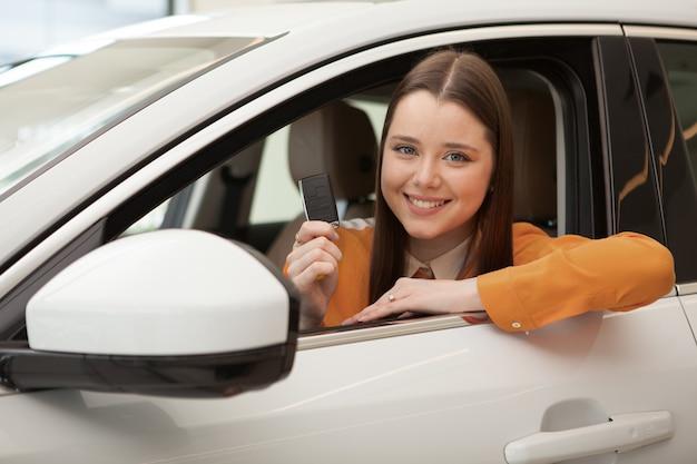 Молодая счастливая женщина-водитель улыбается в камеру, держа ключ от машины, сидя в своем автомобиле