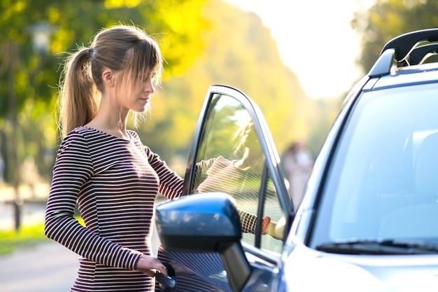 Молодая счастливая женщина-водитель, стоящая возле своей машины на городской улице летом. направления путешествия и транспортная концепция.
