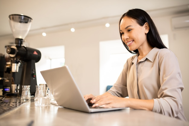 Молодая счастливая женщина-предприниматель сидит на рабочем месте перед ноутбуком во время серфинга в сети для творческих идей
