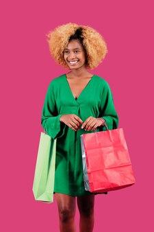 Молодая счастливая покупательница держит красочные сумки после покупок на распродаже в черную пятницу.