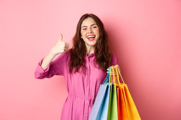 若い幸せな女性の買い物客は、親指を立てて、良い割引に満足し、販売中のスタッフを購入し、買い物袋を持って、満足しているピンクの壁に微笑んでいます。