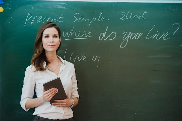 Молодая счастливая учительница с таблеткой цифров в классе.