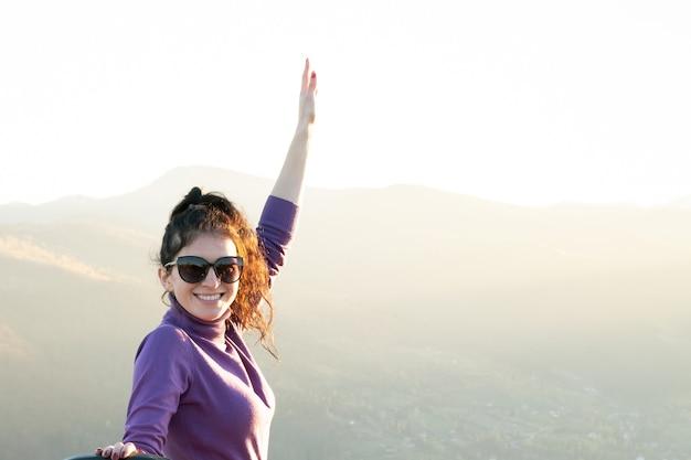 Молодая счастливая женщина с поднятой рукой, наслаждаясь теплым вечером заката в горах лета.